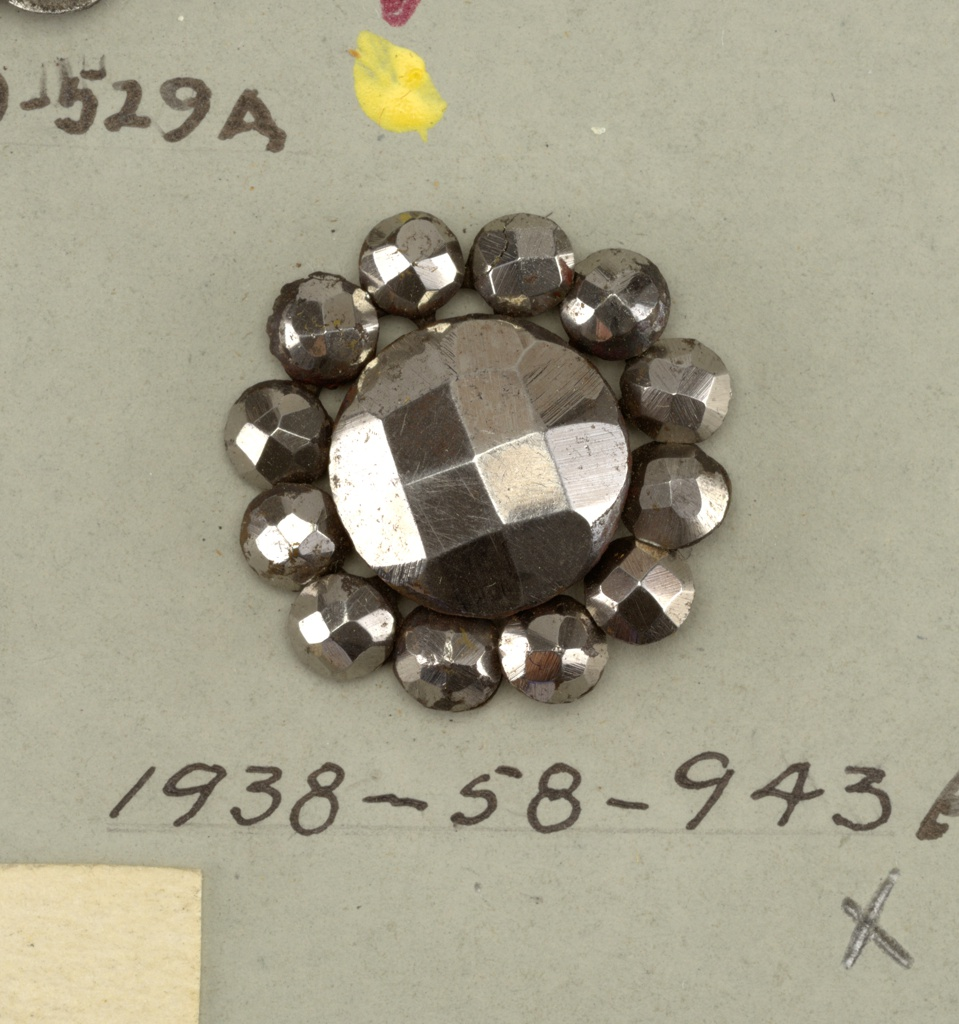 button of cut steel with central bead surrounded by twelve smaller - for other buttons from this set see: 1938-58-940-b/t, which are deaccessioned.  On card 64