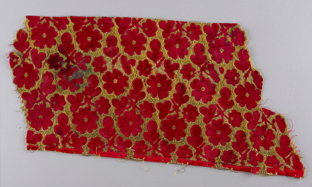 Red allover cut velvet pattern of small blossoms arranged in offset rows - the slant of the flower alternating from row to row. Background is gold.