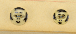 2 buttons resembling calico button of the 19th century - circular buttons -  f, g /: black markings to form a face.  On Cooper Union Exhibition card 1