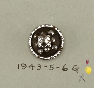 a/: stud of black glass with facetted top and two feet - b,c/:circular steel buttons with edge cut in scallops and in each scallop and in the center a facetted steel boss - d/: circular, flat wooden buttons decorated with carving and circular ornaments of cut steel - g/: circular button with ornament and rim of cut steel -h/: circular button of steel with facetted boss in center and others forming ring at edge with openwork section between - i/: button with brilliants [of two sized] set in three rings around central stone. For other objects from the original set accession numbered 1943-5-6-a/k, see also: 1943-5-6-e,f,j [deaccessioned], and 1943-5-6-k [deaccessioned].  Component -b is on Cooper Union Exhibition card 4 Component -c is on card 58 Component -d is on card 37 Components -g,-h are on card 64 Component -i is on card 19
