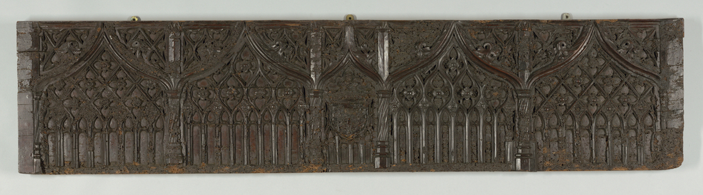 Front of a chest, with architectural decoration in the Flamboyant style: five huge arcades, of which the center is smaller, carved with tracery; shield overlaid upon tracery of center arcade.