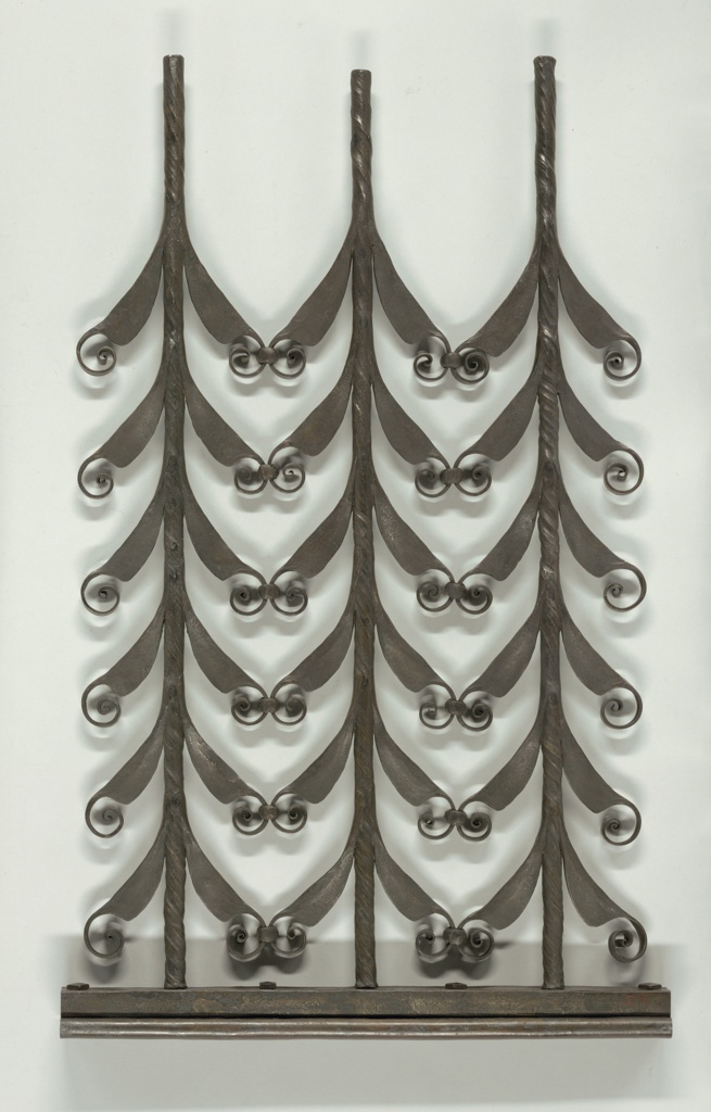 This study or design of black wrought iron is composed of three vertical stylized branches with small curls growing out of V-shaped leaves that line the branches, connected at the curls.