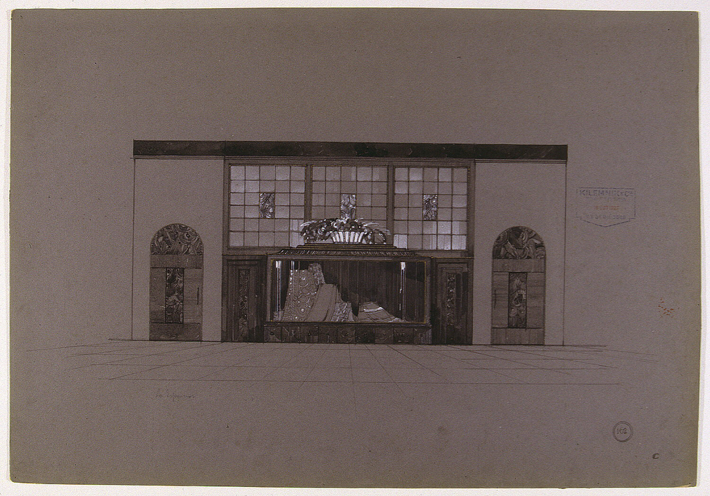 Facade with central projecting vitrine (displaying draped fabrics) on marble dado.  Above vitrine,  three main window frames, each containing rows of small, square glass  panes with a central ornamental plaque (in glass, metal or ceramic?).  At the bottom of the central window  (on top of the vitrine)is a glass or silver basket with  flowers.  On either side of central vitrine are two arched doors  or niches with panels of geometric decoration.