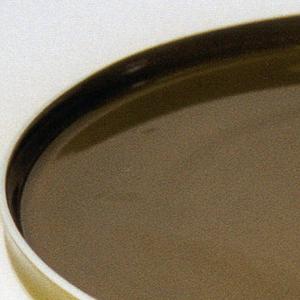 Flat circular form with slightly concave upright rim; white body glazed dark green on interior, green on exterior rim.