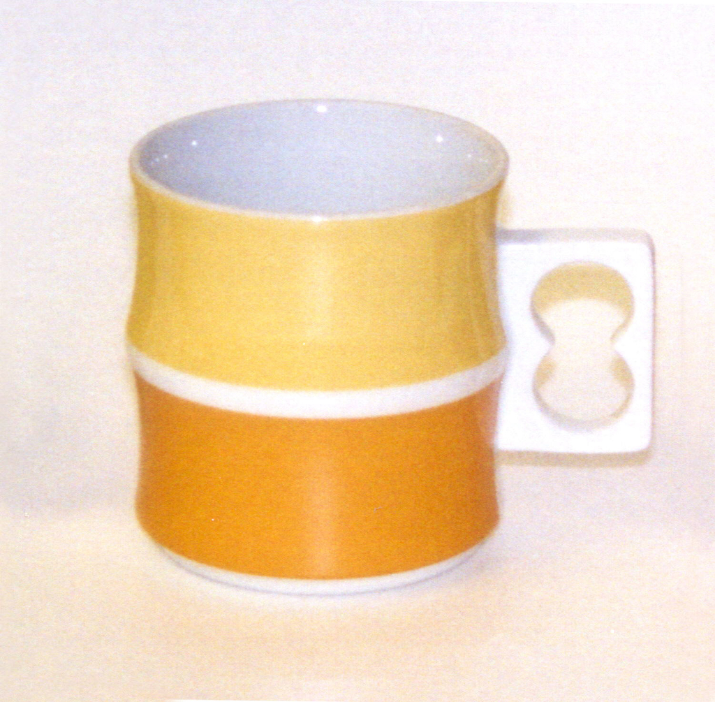Cylindrical body formed of two concave sections, one above, the other, white pierced rectangular handle on side; white body, exterior of top section glazed in yellow, bottom section in light orange.