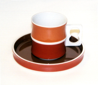 Cup (a): cylindrical white body formed of two concave sections, one above the other, white pierced rectangular handle on side; exterior of top section glazed in orange, bottom section in cinnamon-brown. Saucer (b): circular form with slightly concave upright rim; white body glazed brown on interior, orange on exterior rim.