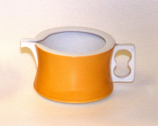 Squat, slightly concave cylindrical body, the exterior glazed orange; white interior and spout, white pierced rectangular handle.