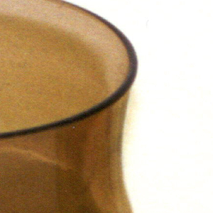 Smokey-brown transparent cylindrical body of two concave sections, one above the other.