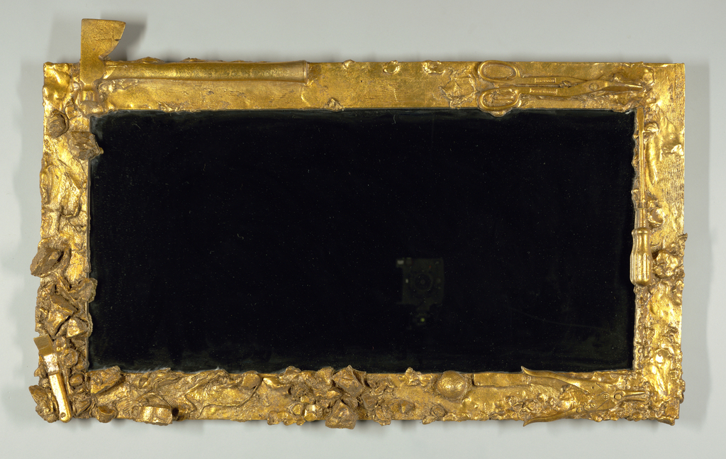 Vertical rectangular mirror in gilt frame incorporating molds of tools, including hatchet and shears.