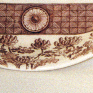 Tapered cylindrical cup (a) with squared handle, the cream-colored ground with brown transfer-printed Japanese-inspired decoration of birds in flight among a tree and flowers, above a geometric-patterned band and flower decoration. Narrow brown geometric-patterned band on inside of rim, geometric pattern on handle.  The circular saucer (b)  transfer-printed with same decoration as cup.