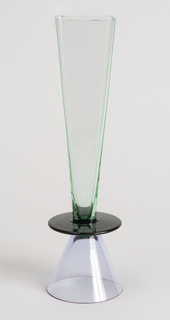 Square flute of light green, thin-walled, transparent glass on dark green disk above short inverted conical foot of violet colored, thin-walled, transparent glass.