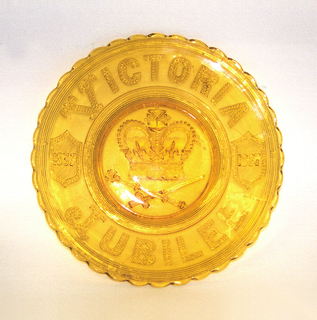 """Clear yellow circular form, the wide scalloped rim molded with the words """"VICTORIA JUBILEE"""" at top and bottom, and two sheilds on left and right bearing the years """"1837"""" and""""1887"""" respectively;  large crown above crossed sword and scepter in well."""