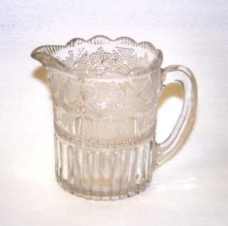 """Clear glass cylindrical form with pressed decoration. Circular scalloped mouth with spout surmounting section decorated with pressed dotted pattern of alternating Maltese cross and fleur-de-lis motifs on swags above the phrase """"JUBILEE OF QUEEN VICTORIA 1837 1887""""; reeded bottom section; ovoid loop handle; crown impressed on underside of base."""