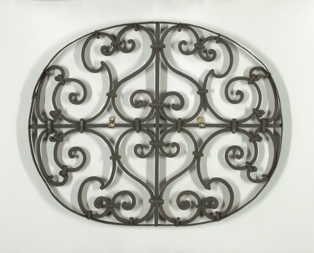 Oval, for a small window. Scroll-work disposed about central vertical and horizontal axial rods.