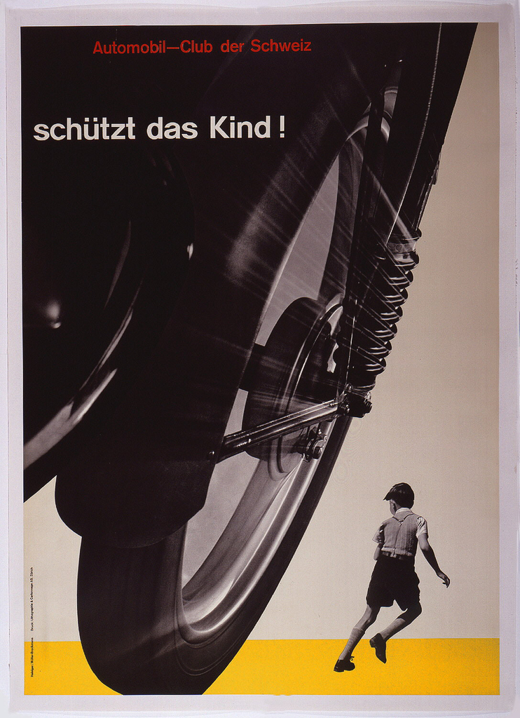 """Black and white photographic image showing a huge motorcycle wheel in left foreground, and a smaller image of a young boy running (seen from behind), in the lower right corner. In order to promote traffic safety, the poster is designed so the vehicle tire threateningly appears to be about to run over the child.Text in red Akzidenz Grotesk type face at upper left: Automobil-Club der Schweiz (Automobile Club of Switzerland); below in white Akizidence Grotesk: """" Schüzt das Kind!"""" Yellow ground across bottom edge."""
