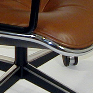 Bucket-form swivel armchair base consisting of post surmounting four splayed supports with casters; brown leather upholstery; black plastic arms.