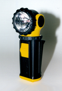 Black ovoid swiveling head cradled in yellow housing on ridged black tubular body (a) with attached clip. Yellow base (b) slides out of body for access to battery compartment.