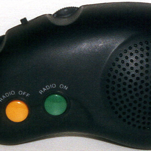 "Bean-shaped black body (a) with  yellow ""off"" and green ""on"" buttons and circular pierced speaker; black plastic strap attached near speaker. Battery compartment cover (b) on reverse."