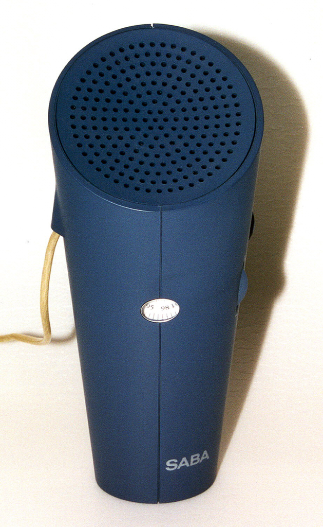 Blue-grey body (a) of tapering cylindrical form, angled concave circular top pierced with holes for speaker; numerical station indicator in center front, on/off/volume dial and tuning dial on right side, flexible antenna cord attached on left.  Circular battery compartment cover (b) on bottom.