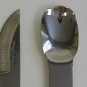 """Lozenge-shaped polished steel form with three upturned tines and """"BE CAST"""" on handle. Part of six-piece picnic set."""