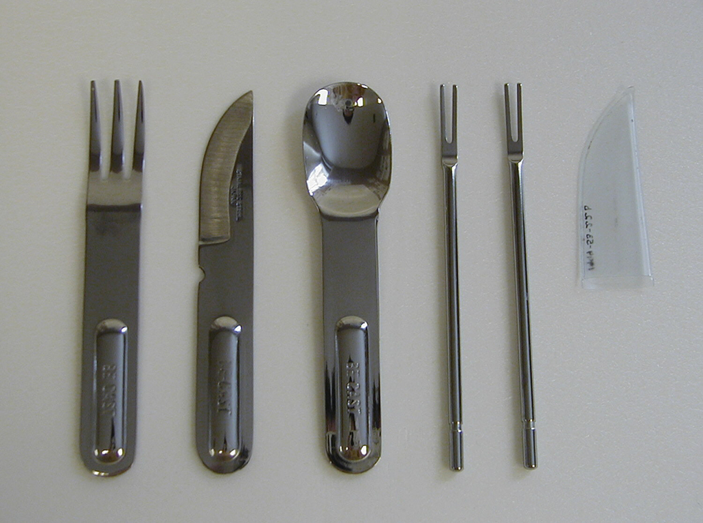 Thin cylindrical shaft of polished steel with two flat tines.  Part of six-piece picnic set.