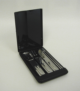 "Case for picnic cutlery 1999-53-21/25.  Black rectangular shape with curved corners; the hinged lid, with raised lozenge-shaped section at left and ""BE CAST US"" logo on upper right, opens to reveal cutlery fitted in sectioned base; each section labled with the name of the corresponding piece: from left to right: spoon, fork, knife, pick, pick."