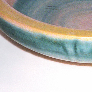 Shallow bowl with curved handles, thick inverted lip in pink, yellow, and turquoise.
