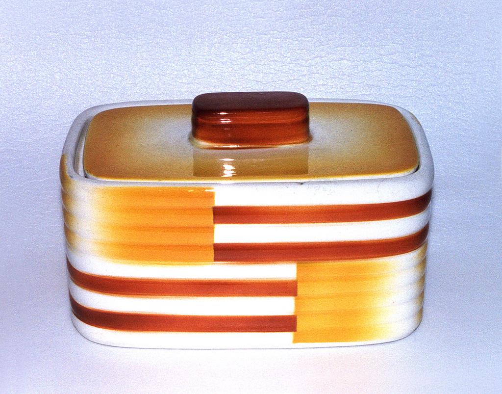 Rectangular box with streamlined corners. Flat lid with rounded rectangular handle. Orange and yellow geometric decoration.