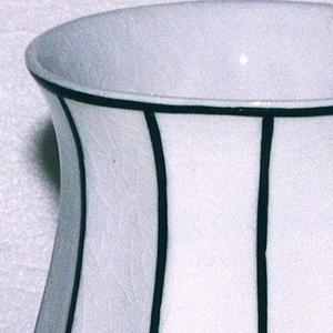 White baluster vase with thin black vertical stripes.