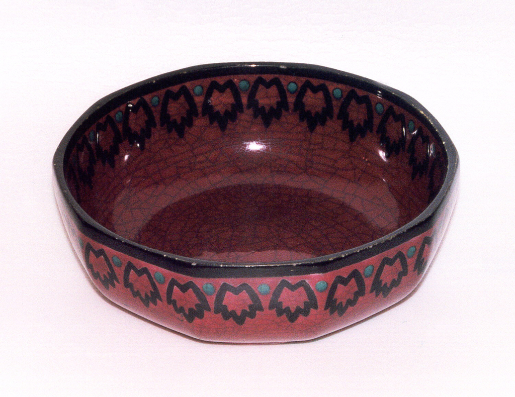 Round bowl on a low foot. Red glaze with crazing. Black rim and repeating pattern of jagged forms and blue dots on interior and exterior.