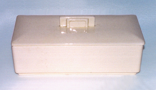 Rectangular light peach box with slight foot; lid with slight convex lines from edge to central finial; finial composed of concentric standing rectangles.