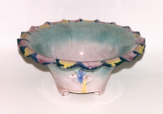 Flaring footed dish with scalloped rim and molded floral motif at center. Pale green and pink ground.