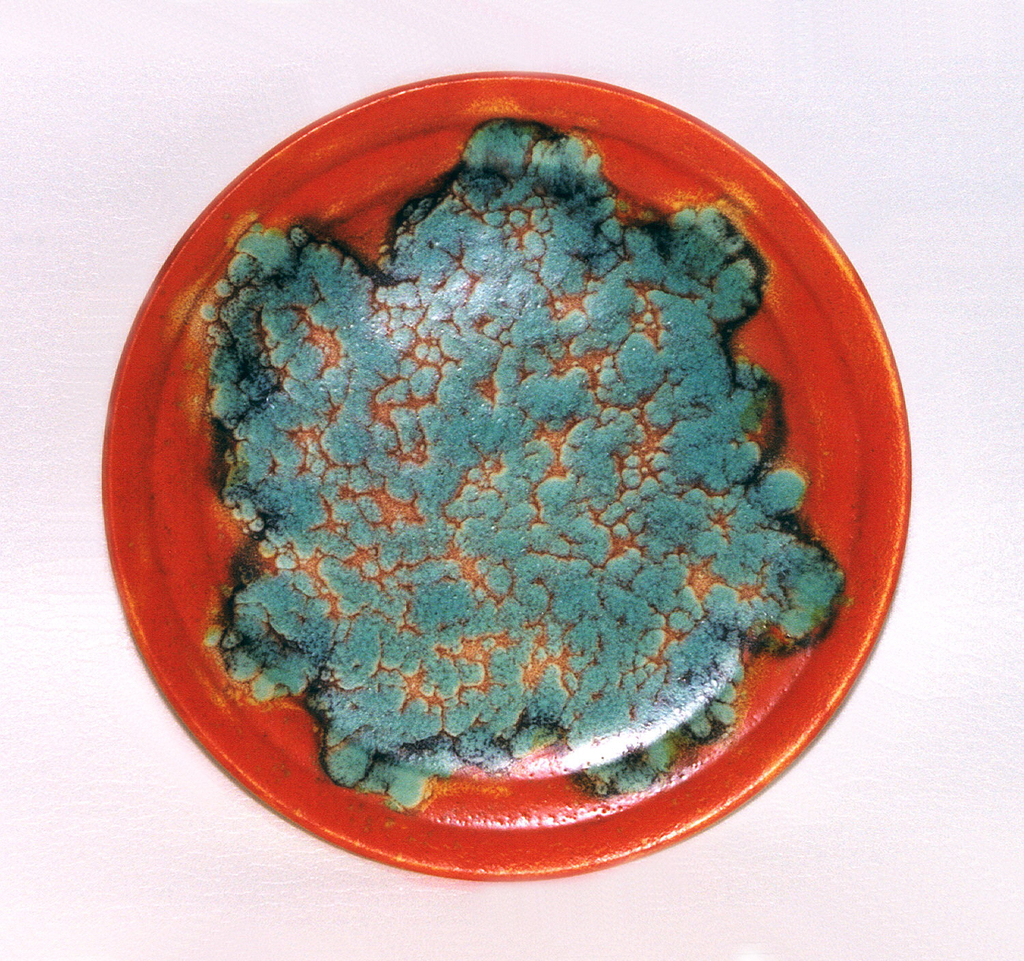 Round plate with flat orange rim. At center, green glaze with orange details.