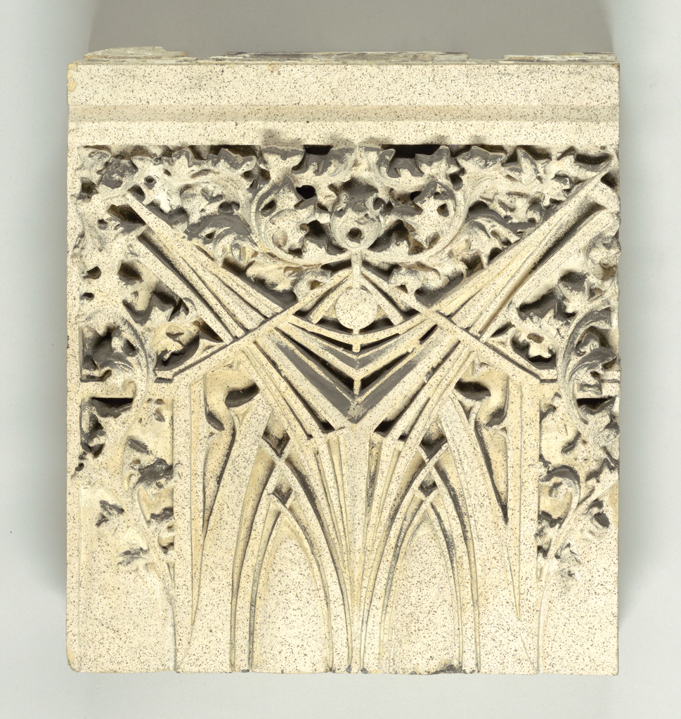 Large square panel of buff-colored terracotta, the surface decorated with one half of vertically oriented design of abstract vegetal motif in lozenge shape (to be set above similar panel to complete design).