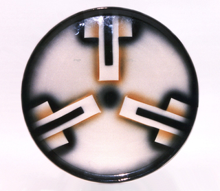 Round with three stepped designs in reserve, surrounded by atomized black and yellow glaze. Black rim and circel at center.