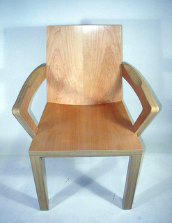 Of thickly constructed honey-colored laminate and veneer, the curving planar seat and back sit firmly on four attenuated rectangular legs;  rectilinear arms rise from either side of the seat and curve back to join the rear legs behind the chair back.