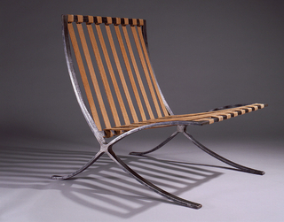 Square frame of flat steel elements with welded joints; the straight horizontal elements at the back and seat joined to curving side elements forming a sweeping X-shape in profile.  Nine orange/tan hemp straps on back, eight on seat, the ends wrapped around the horizontal steel elements and secured with screws. The rough steel surface with traces of black paint or lacquer.