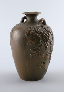 Buff clay body, cast.  Amphora form with flaring rim.  High relief decoration of grape clusters and leaves on each side below vine-formed handles.  Electro-deposit of bronze covers surface and foot rim portion of bottom.  Green patination, slightly streaked.