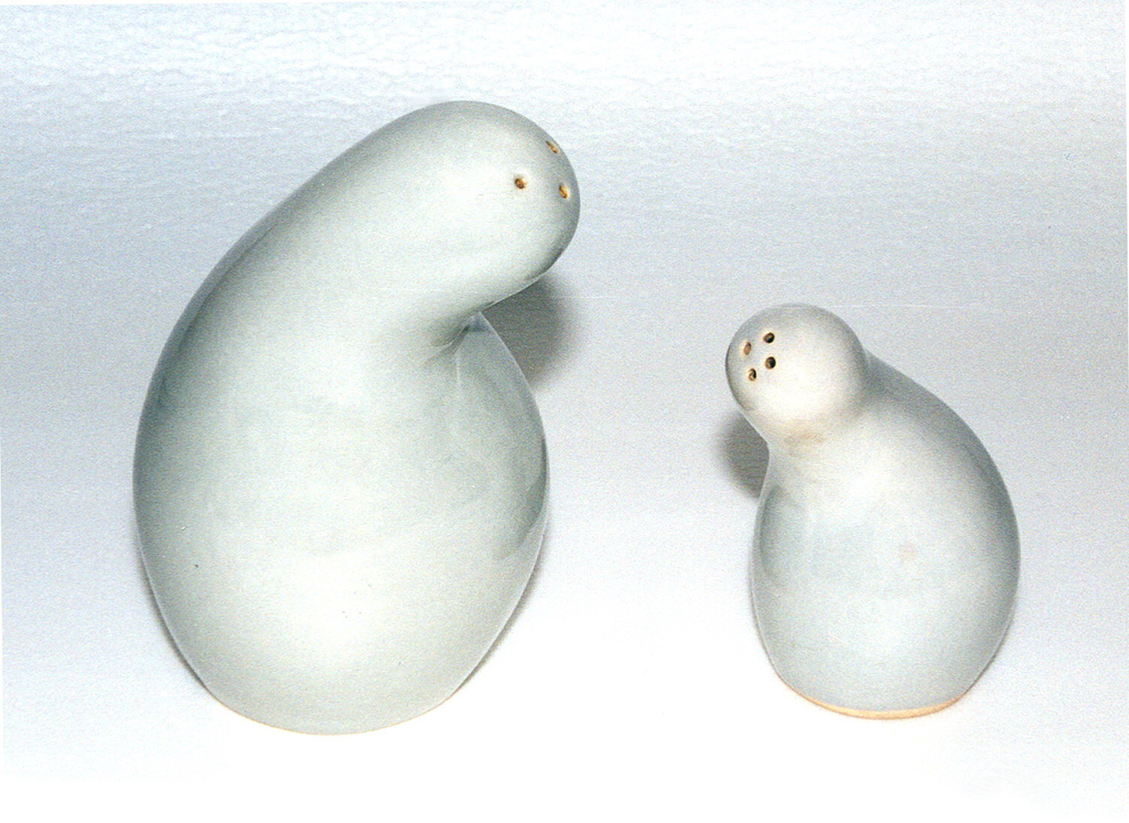 Gray glazed gourd-like form (a) having bulbous lower section tapering into a curved neck; the rounded top with three holes set off-center; cork stopper (b) in bottom.