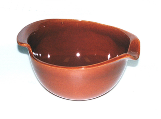 Deep circular bowl with wide rim, the irregular edge turned out to form a spout and hand grip. Rust colored glaze.