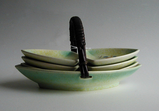 Oval dish with pointed ends, raised bottom rim; curved dark brown ratan handle.  Cream ground airbrushed yellow to green with pattern of wavy and straight crossed black lines, three wavy brown lines, and three blue dots.