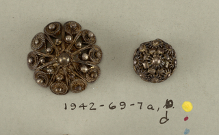 three circular butons with silver shanks - a/: slightly convex ornament composed of ten scrolls of silver wire arranged around outside with lines reaching in toward center; small ball in center with two concentric rings of ten balls each.  c and d/: globular button in design of conventionalized flowers.  Component -a and d is on card 48 Component -c is on Cooper Union Exhibition card 4