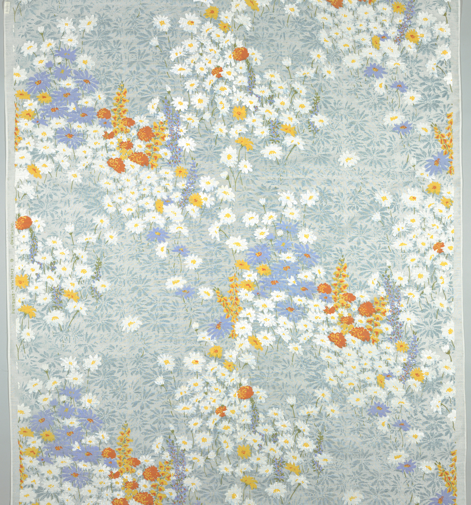 Masses of daisies and other flower are printed in white, yellow, orange, and lavender against a woodblock ground of scattered blue-grey daisies.