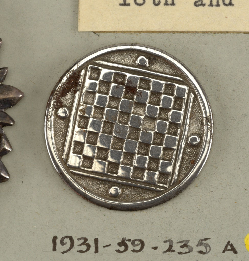 Button ornamented in design of checker board and four checkers. Steel shank.  On card 48