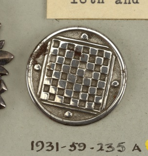 Button ornamented in design of checker board and four checkers. Steel shank.