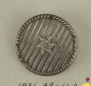 set of six large and four small round lead buttons - raised design; rope edge; stripes of fine beading across button; central six-petalled blossom.  Component -d is on card 50 Component -f is on Cooper Union Exhibition card 5