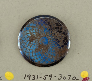 circular, flat button with bevelled edges ornamented with inscised overlapping ovals arranged as a may-petalled flower.  On card 48