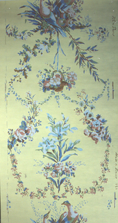 Pair of doves, from which is suspended a basket containing flowers, below this is a branch of lilies (?). These elements are connected by floral garlands. Printed in colors on a yellow ground.