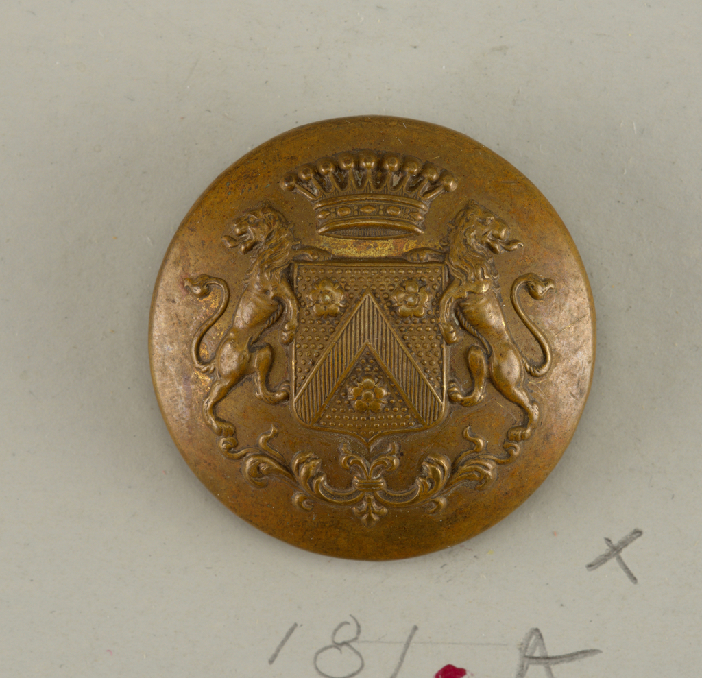 "convex button with ornament of a shield with heraldic devices, lion supporters standing on leaf scrolls and, at top, a crown - brass back and shank - on reverse, ""Carette and Philipponnat Paris.""  On card H"