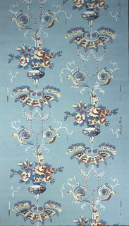Arabesque format, vase with flowers, centered between scrolling tendrils, above, and bat wing motif with strung beads, below. Printed in colors on a teal ground.